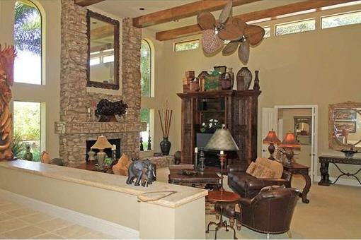 Salón con chimenea y ventiladores de techo en Fort Myers